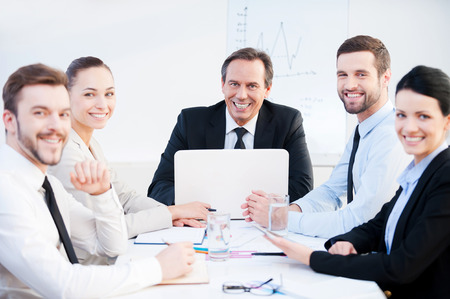 meeting place: Confident business team. Group of confident business people in formalwear sitting at the table together and smiling Stock Photo