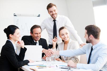 Willkommen an Bord! Gruppe überzeugte Geschäftsleute in formalwear am Tisch sitzen zusammen und lächeln, während zwei Männer Händeschütteln Standard-Bild