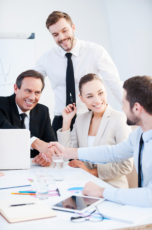 business person: Congratulations! Two confident businessmen handshaking and smiling while sitting at the table together with their colleagues