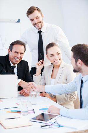 Enhorabuena! Dos hombres de negocios confidentes apretón de manos y sonriendo mientras está sentado en la mesa junto con sus colegas Foto de archivo - 34391308