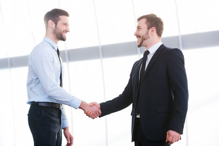 Sealing a deal. Two cheerful business men shaking hands and smiling while standing indoors Archivio Fotografico