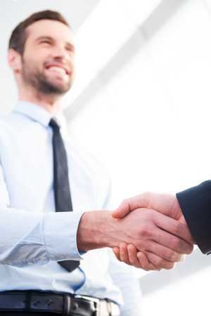 Good deal! Low angle view of confident businessman shaking hand to his business partner and smiling Stock Photo
