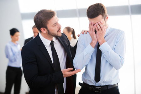 office attire: Consoling his hopeless colleague. Young businessman consoling his depressed colleague with people standing in the background Stock Photo