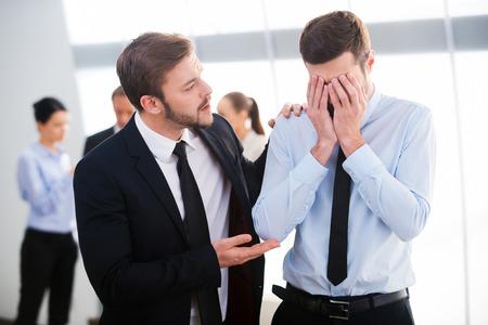 empleado de oficina: Reconfortante su colega sin esperanza. Joven empresario que consuela a su colega deprimido con personas de pie en el fondo Foto de archivo