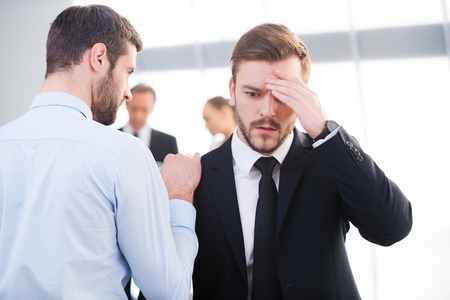 shoulder problem: Bad news. Rear view of young businessman consoling his depressed colleague and holding hand on his shoulder with people standing in the background Stock Photo