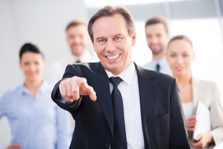 I choose you! Confident mature businessman pointing you and smiling while his colleagues standing in the background photo