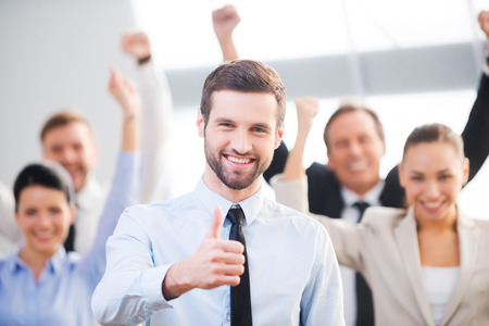 gente exitosa: Sentirse seguro en su equipo. Hombre de negocios feliz que muestra el pulgar hacia arriba y sonriendo mientras sus colegas de pie en el fondo