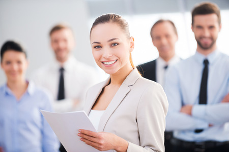 man looking out: Confident businesswoman. Attractive young businesswoman holding documents and smiling while his colleagues standing in the background