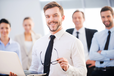 Supporting your business. Confident young businessman holding laptop and smiling while his colleagues standing in the background Stock Photo