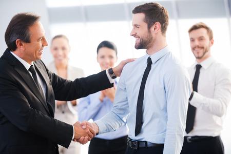 traje: Buen trabajo! Dos hombres de negocios alegre dando la mano, mientras que sus colegas aplaudiendo y sonriendo en el fondo