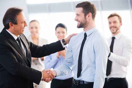 white work: Good job! Two cheerful business men shaking hands while their colleagues applauding and smiling in the background