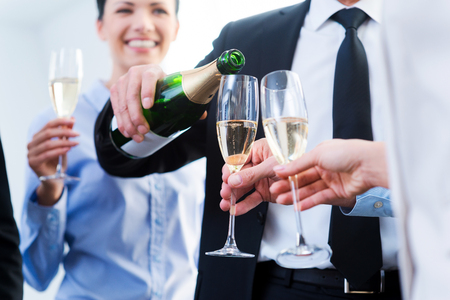office party: Celebrating business success. Close-up of business people holding flutes while man pouring champagne