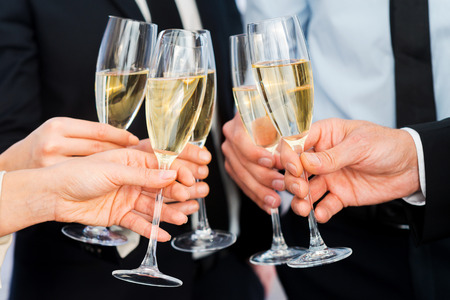 成功に乾杯。シャンパン フルートを保持しているビジネス人々 のクローズ アップ