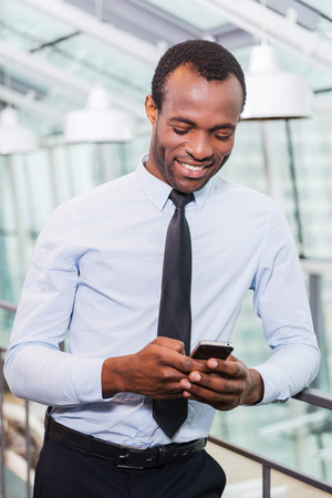 black person: Typing business message. Cheerful young African man in shirt and tie holding mobile phone and looking at it with smile while standing indoors