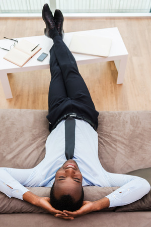 Total relaxation. Top view of happy young African man in formalwear lying on the couch with his legs on a desk and hands behind head photo