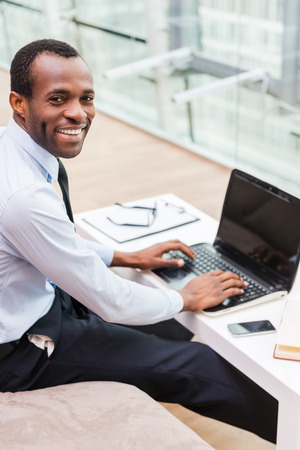 Working with pleasure. Top view of young African man in formalwear working on laptop and smiling while sitting at his working place photo