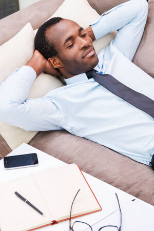 Relaxing after work. Top view of handsome young African man in shirt and tie holding hands behind head and keeping eyes closed while lying on the couch photo