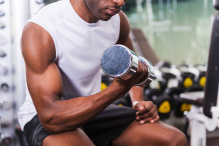 only the biceps: Bodybuilding. Cropped image of young African man training with dumbbell in gym
