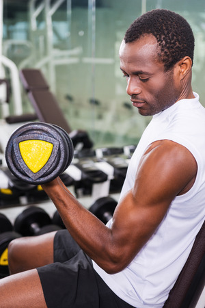 only the biceps: Training with dumbbells. Handsome young African man training with dumbbell in gym