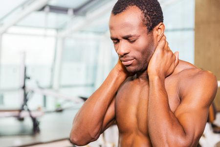 tired man: Feeling neckache after workout. Frustrated young African man touching his neck and expressing negativity while standing in gym Stock Photo