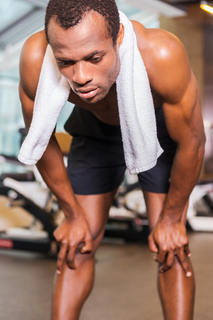 over shoulders: Feeling tired after workout. Tired young African man with towel over shoulders leaning at his knees while standing in gym Stock Photo