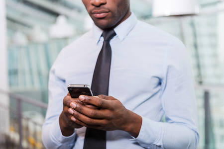 Businessman typing message. Cropped image of young African man in shirt and tie texting on his mobile phone while standing indoors Stock Photo