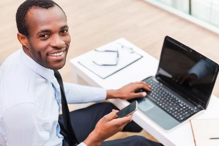 Arbeiten mit Lächeln. Draufsicht der jungen afrikanischen Mann in: Abendkleidung auf Laptop und lächelt, während sitzt an seinem Arbeitsplatz