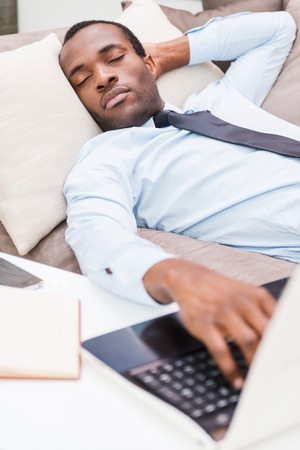 Tired and overworked. Handsome young African man in formalwear holding hand on laptop keyboard while sleeping on the couch photo