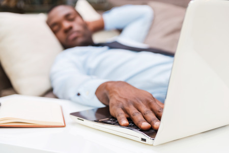 Overworked businessman. Young African man in formalwear holding hand on laptop keyboard while sleeping on the couch photo