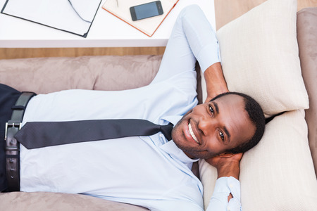 Relaxing after long day working. Top view of handsome young African man in shirt and tie holding hands behind head and smiling while lying on the couch photo