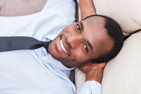 Taking time to for a minute break. Top view of handsome young African man in shirt and tie holding hands behind head and smiling while lying on the couch photo