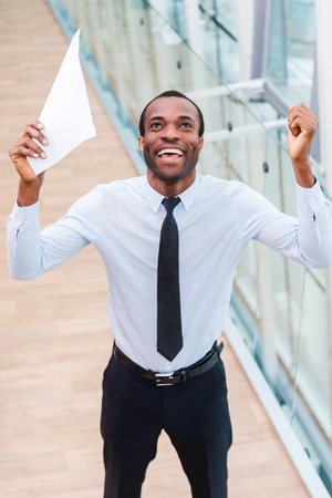 of african descent: I did it! Top view of happy young African man in shirt and tie holding paper and keeping arms raised Stock Photo