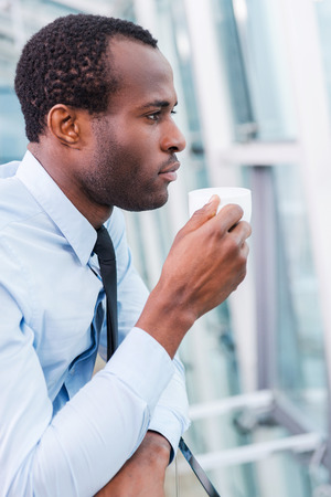 black business men: Thinking about solution. Side view of thoughtful young African man in shirt and tie holding coffee cup and looking away Stock Photo