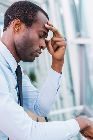 Hopeless and depressed. Side view of frustrated African man in shirt and tie touching his face and keeping eyes closed photo
