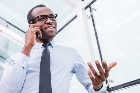 business person: Business talk. Low angle view of confident young African man in shirt and tie talking on the mobile phone and gesturing