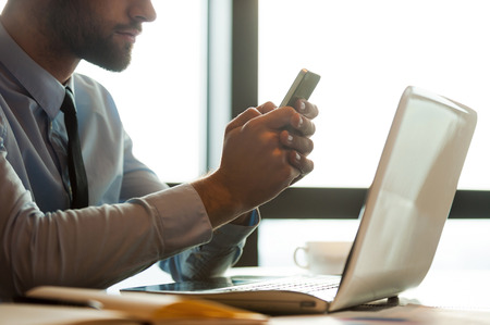 cropped image: Typing business message. Cropped image of young man in shirt and tie holding mobile phone and looking at it while sitting at his working place