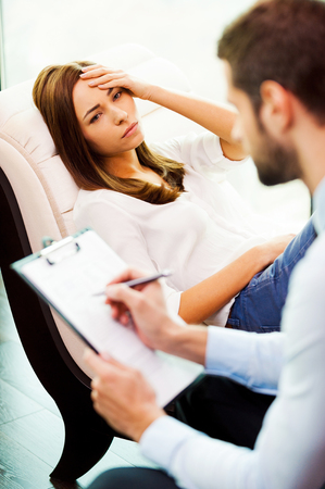doctor writing: Feeling hopeless and depressed. Depressed young woman sitting at the chair and holding hand on head while young man sitting close to her and writing something in his clipboard Stock Photo