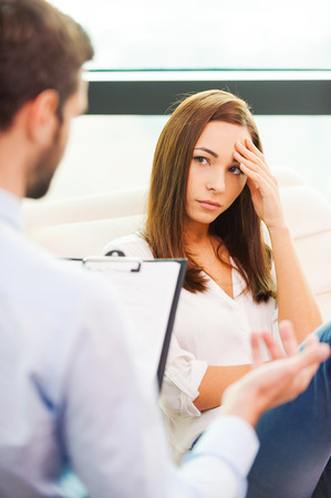 consoling: She needs to be consoled. Worried young woman sitting at the chair and holding hand on head while male psychiatrist sitting in front of her and gesturing