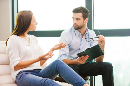 Sharing problems with psychiatrist. Worried young woman sitting at the chair and gesturing while male psychiatrist sitting close to her and holding clipboard Stock Photo