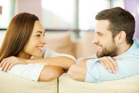 amantes: Disfrutando de uno al otro. Hermosa pareja de j�venes amantes sentados juntos en el sof� y mirando el uno al otro con una sonrisa
