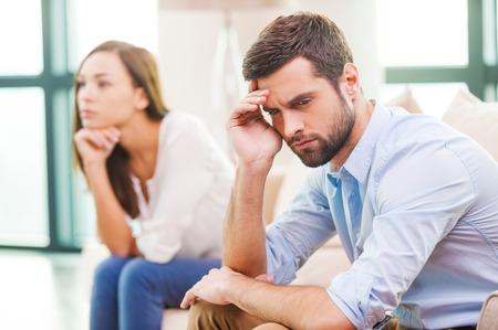 Ruptura de relaciones. Hombre joven deprimido de la mano en la cabeza y mirando a otro lado mientras que la mujer se sienta detrás de él en el sofá