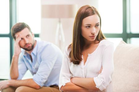 personas discutiendo: Dificultades de relación. Deprimido joven mantener los brazos cruzados y mirando a otro lado mientras que el hombre sentado detrás de ella en el sofá