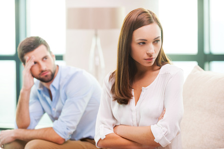 Relationship difficulties. Depressed young woman keeping arms crossed and looking away while man sitting behind her on the couch