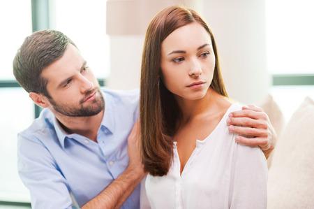 depresi�n: Reconfortante su novia deprimida. Mujer joven deprimido mirando a otro lado mientras que el hombre sentado detr�s de ella en el sof� y consol�ndola