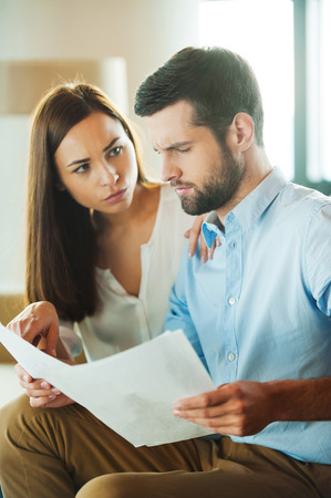 Financial problems. Frustrated young man holding papers and looking at them while woman sitting close to him and pointing document photo