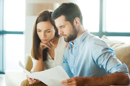 persona pensando: El examen de los documentos juntos. Concentrado joven hombre con documentos y mirarlos mientras que la mujer se sienta cerca de �l y de la mano en la barbilla