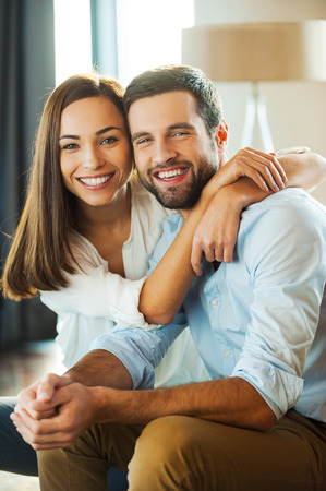 parejas enamoradas: Feliz de estar juntos. Hermosa pareja de jóvenes amantes sentados juntos en el sofá mientras que la mujer abrazando a su novio y sonriente