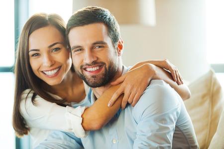 parejas enamoradas: Disfrutando cada minuto juntos. Hermosa pareja de jóvenes amantes sentados juntos en el sofá mientras que la mujer abrazando a su novio y sonriente
