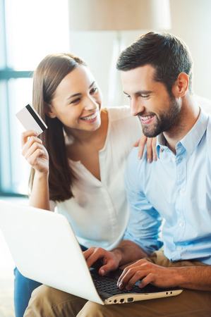 Shopping online together. Beautiful young loving couple shopping online together while woman holding credit card and smiling