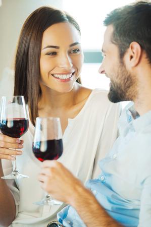 jovenes tomando alcohol: Celebrando el amor. Hermosa pareja amorosa joven sentado cerca unos de otros y beber vino tinto Foto de archivo